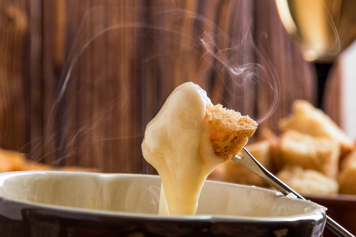 Close up, macro. Traditional french cheese fondue. Crouton dipped into stemy-hot cheese fondue on a long-stemmed fork. Winter seasonal meal. Copy space.